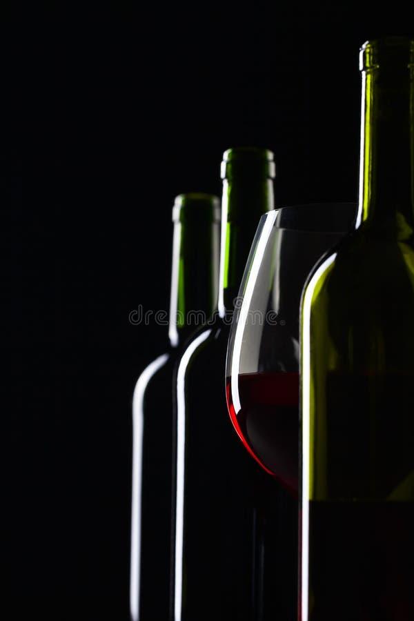 Μπουκάλια και ποτήρι του κόκκινου κρασιού σε ένα μαύρο υπόβαθρο στοκ φωτογραφία με δικαίωμα ελεύθερης χρήσης