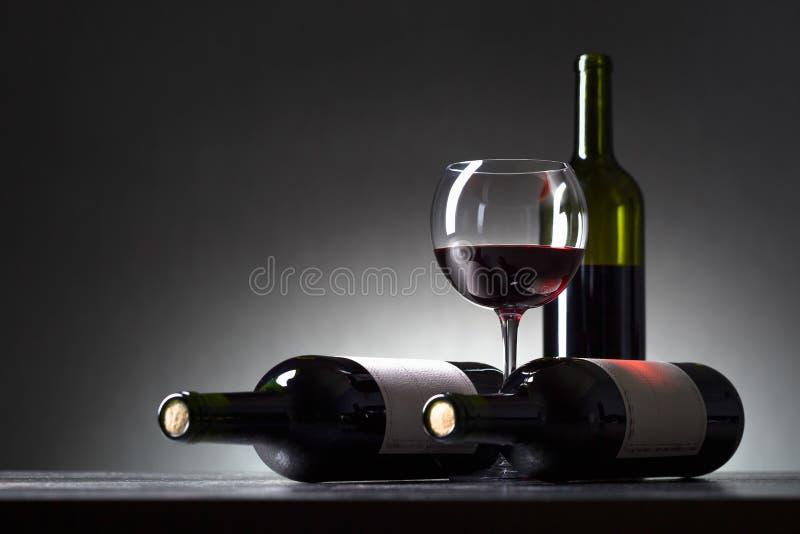 Μπουκάλια και ποτήρι του κόκκινου κρασιού στοκ φωτογραφίες με δικαίωμα ελεύθερης χρήσης
