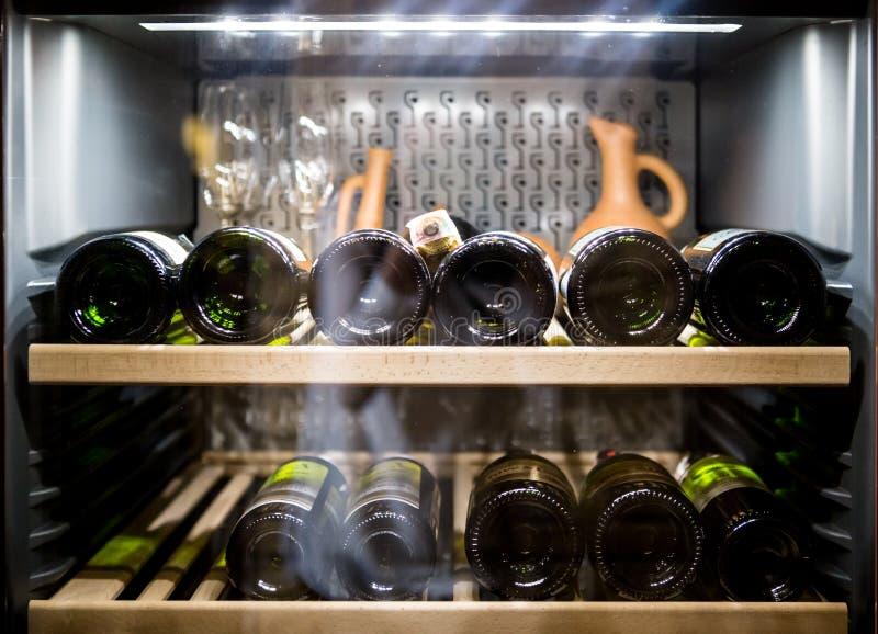 Μπουκάλια κρασιού που δροσίζουν στο ψυγείο στοκ εικόνα