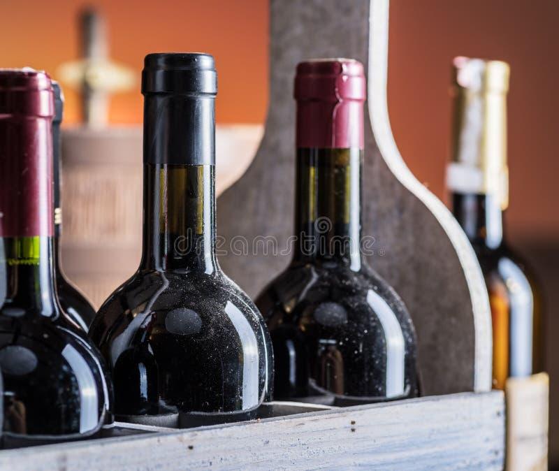 Μπουκάλια κρασιού στο ξύλινο κλουβί και το δρύινο βυτίο κρασιού στοκ εικόνες