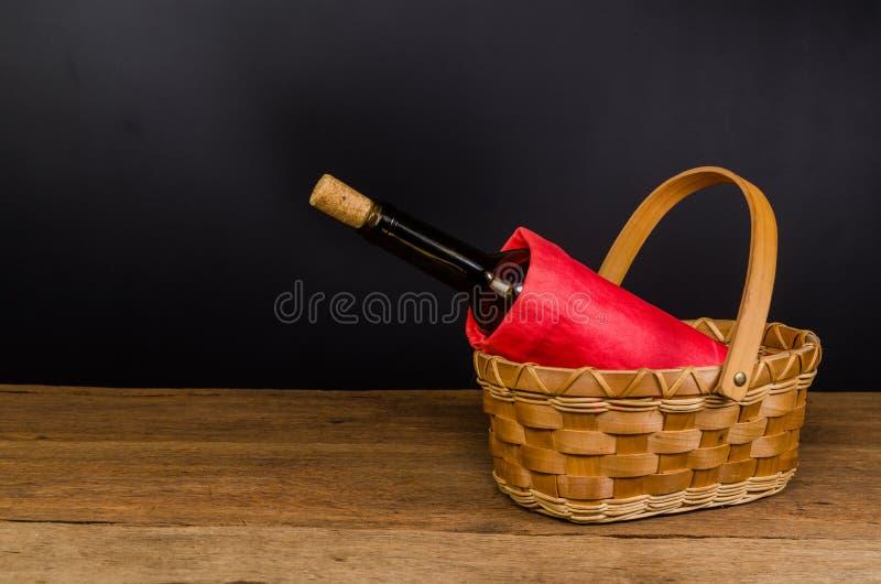 μπουκάλια κόκκινου κρασιού στο ψάθινο καλάθι στον ξύλινο πίνακα στοκ εικόνα