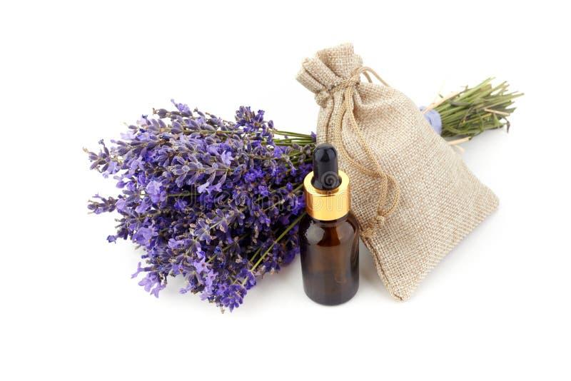 Μπουκάλια με ελαίου και lavender αρώματος τα λουλούδια που απομονώνονται στο λευκό στοκ φωτογραφίες