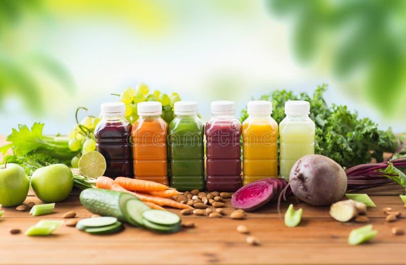 Μπουκάλια με τα διαφορετικά φρούτα ή τους φυτικούς χυμούς στοκ φωτογραφία