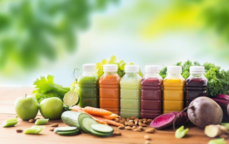 Μπουκάλια με τα διαφορετικά φρούτα ή τους φυτικούς χυμούς στοκ εικόνα