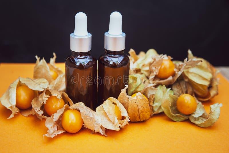 Μπουκάλια με το έλαιο physalis και τους νωπούς καρπούς στο πορτοκάλι στοκ εικόνες
