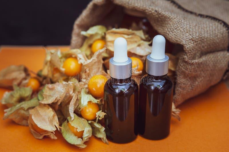 Μπουκάλια με το έλαιο physalis και τους νωπούς καρπούς στο πορτοκάλι στοκ φωτογραφία με δικαίωμα ελεύθερης χρήσης