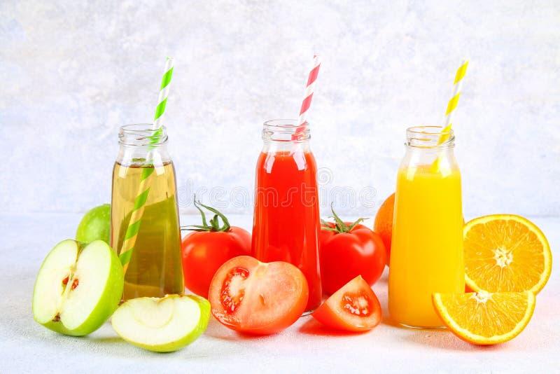 Μπουκάλια με το φρέσκο πορτοκάλι, το μήλο, το χυμό ντοματών και χρωματισμένα tubules σε έναν γκρίζο συγκεκριμένο πίνακα στοκ φωτογραφία