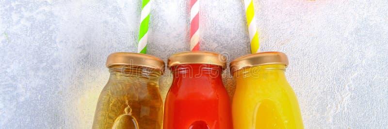 Μπουκάλια με το φρέσκο πορτοκάλι, το μήλο, το χυμό ντοματών και χρωματισμένα tubules σε έναν γκρίζο συγκεκριμένο πίνακα Φρούτα κα στοκ φωτογραφία με δικαίωμα ελεύθερης χρήσης