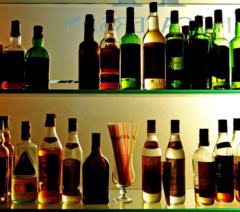 Μπουκάλια του κρασιού και των ποτών στο φραγμό στοκ εικόνα