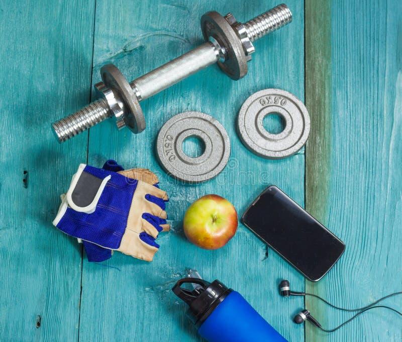 Μπουκάλι αθλητικών στοιχείων, αλτήρες, γάντια στο αθλητικό δάπεδο στοκ φωτογραφία