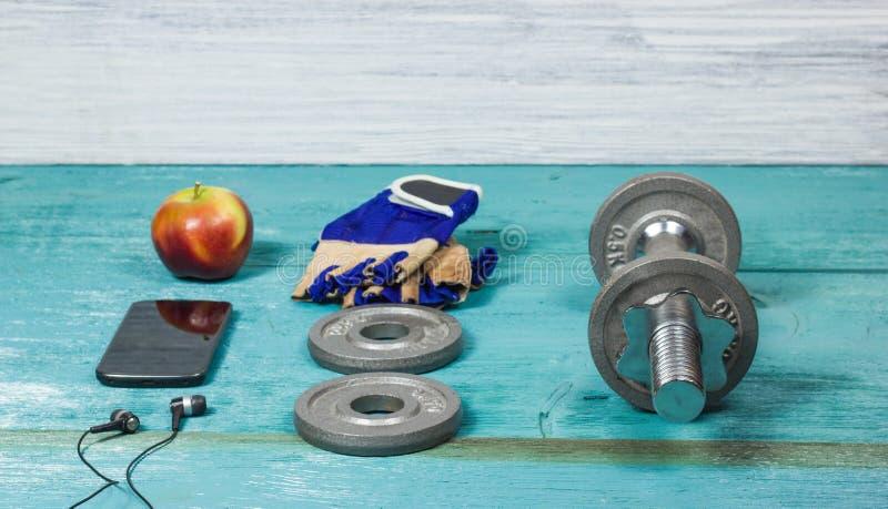 Μπουκάλι αθλητικών στοιχείων, αλτήρες, γάντια στο αθλητικό δάπεδο στοκ εικόνες με δικαίωμα ελεύθερης χρήσης