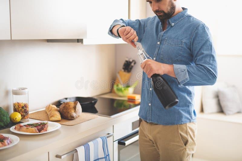 Μπουκάλι ανοίγματος νεαρών άνδρων του κρασιού στεμένος στην κουζίνα στο σπίτι στοκ εικόνα με δικαίωμα ελεύθερης χρήσης