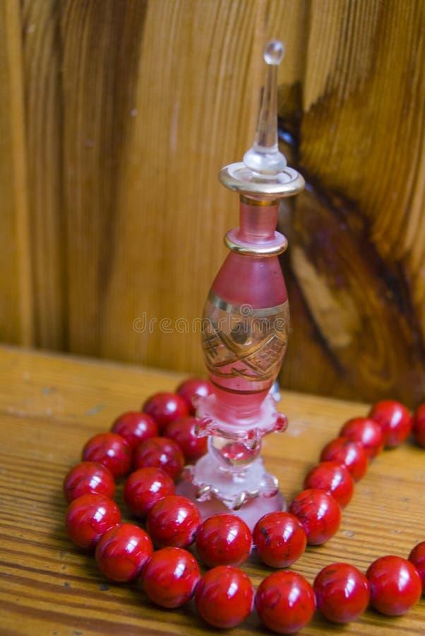 Μπουκάλι αρώματος με τις κόκκινες χάντρες πετρών στοκ εικόνα με δικαίωμα ελεύθερης χρήσης