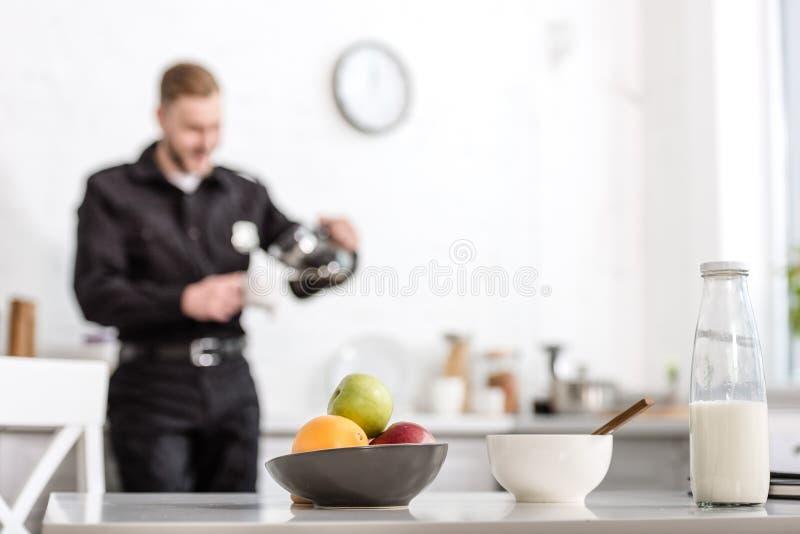 μπουκάλι γάλακτος, κύπελλο των φρούτων στον πίνακα κουζινών και αστυνομικός στοκ φωτογραφίες