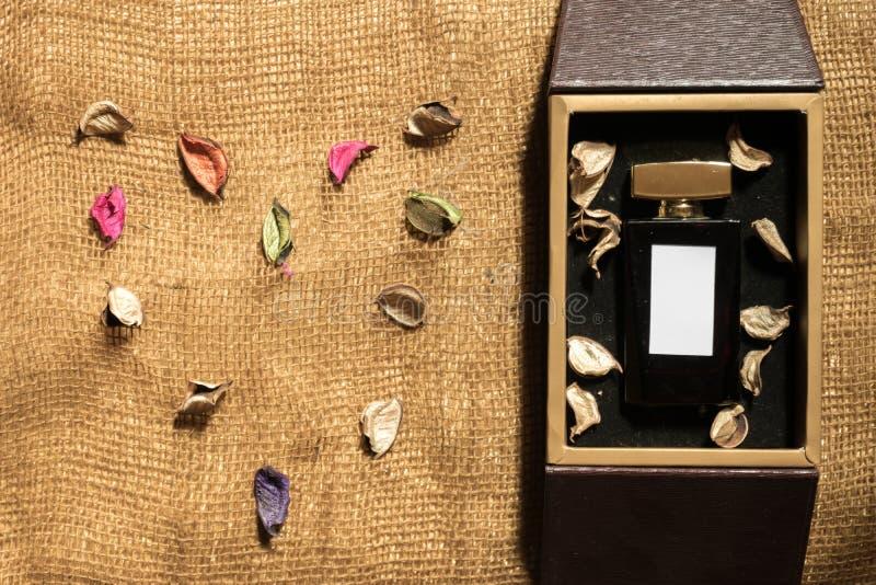 Μπουκάλι γυαλιού αρώματος μέσα στο χρυσό κιβώτιο δώρων στοκ εικόνα