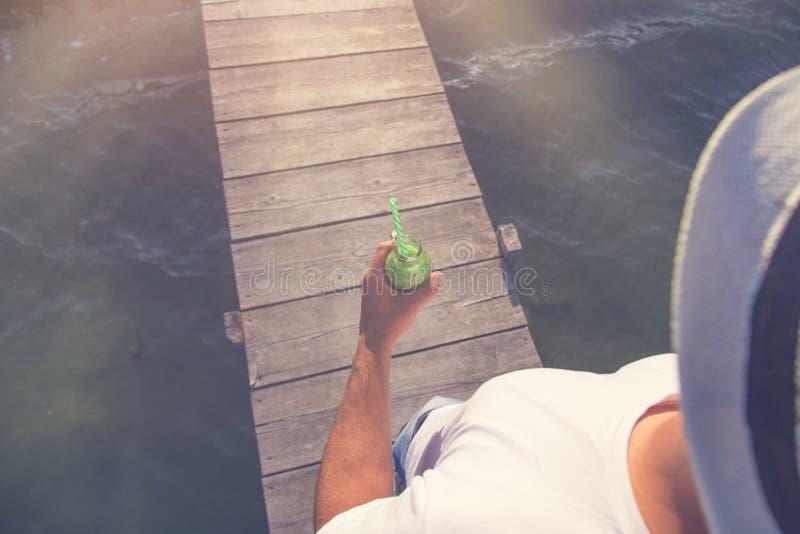 Μπουκάλι γυαλιού εκμετάλλευσης ατόμων του χυμού και του περπατήματος ακτινίδιων στο ξύλινο έγγραφο στοκ εικόνα με δικαίωμα ελεύθερης χρήσης