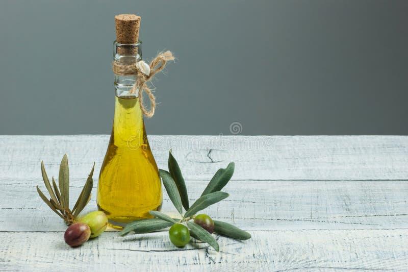 Μπουκάλι γυαλιού του ελαιολάδου με τους ακατέργαστους τουρκικούς σπόρους ελιών και του φύλλου στον άσπρο αγροτικό εκλεκτής ποιότη στοκ εικόνες