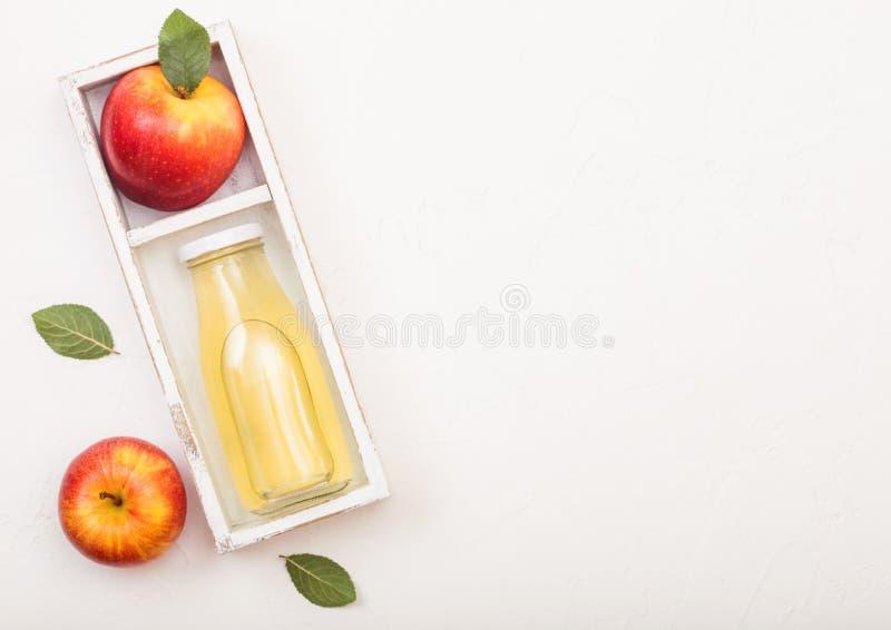 Μπουκάλι γυαλιού του φρέσκου οργανικού χυμού μήλων με τα ρόδινα γυναικεία κόκκινα μήλα στο εκλεκτής ποιότητας κιβώτιο στο ξύλινο  στοκ φωτογραφίες
