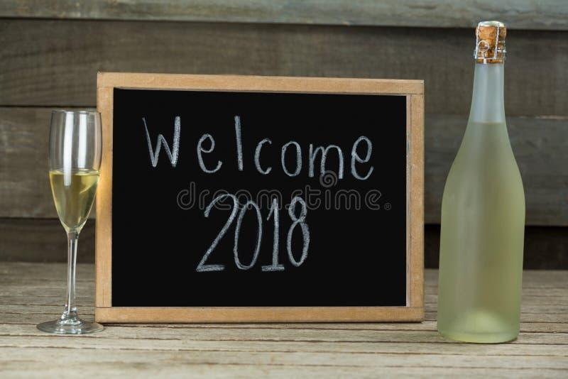Μπουκάλι και γυαλί CHAMPAGNE που κρατιούνται εκτός από την πλάκα με την υποδοχή 2018 στοκ εικόνες