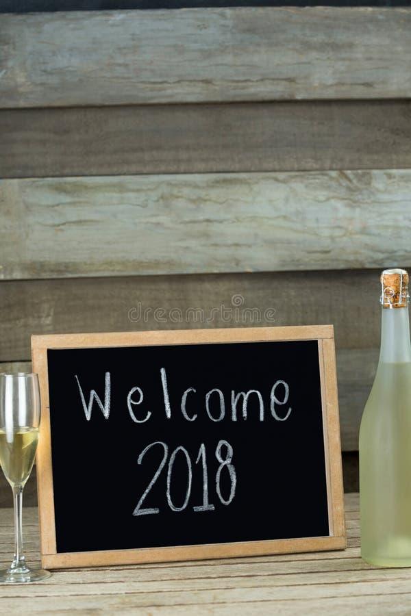 Μπουκάλι και γυαλί CHAMPAGNE που κρατιούνται εκτός από την πλάκα με την υποδοχή 2018 στοκ εικόνα με δικαίωμα ελεύθερης χρήσης