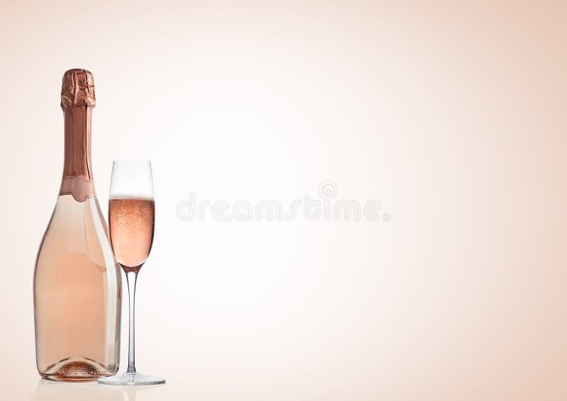 Μπουκάλι και ποτήρι της ρόδινης ροδαλής σαμπάνιας στο ροζ στοκ φωτογραφία με δικαίωμα ελεύθερης χρήσης