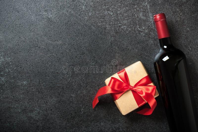 Μπουκάλι κόκκινου κρασιού και κιβώτιο δώρων στο μαύρο υπόβαθρο στοκ εικόνα