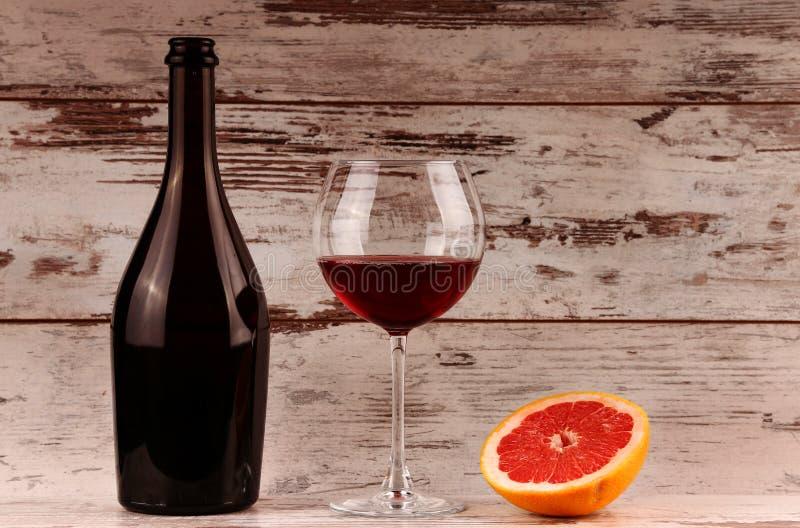 Μπουκάλι κόκκινου κρασιού σε ένα ξύλινα μήλο και ένα ρόδι στοκ εικόνες