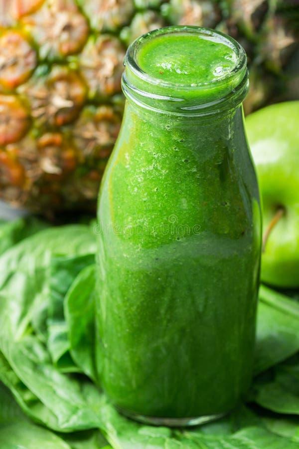 Μπουκάλι με τον πράσινο φρέσκο ακατέργαστο καταφερτζή από τα φυλλώδη κολοκύθια ακτινίδιων μπανανών ανανά μήλων φρούτων λαχανικών  στοκ φωτογραφία με δικαίωμα ελεύθερης χρήσης