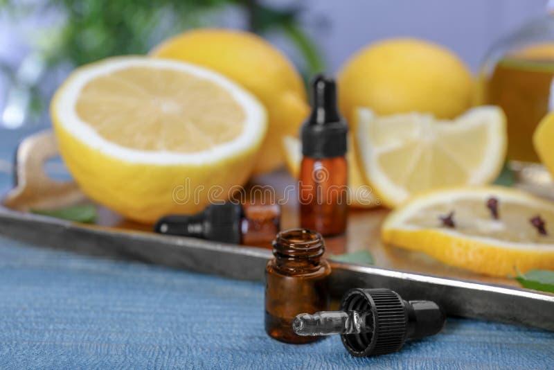 Μπουκάλι με το ουσιαστικό έλαιο και τα θολωμένα λεμόνια στοκ εικόνες