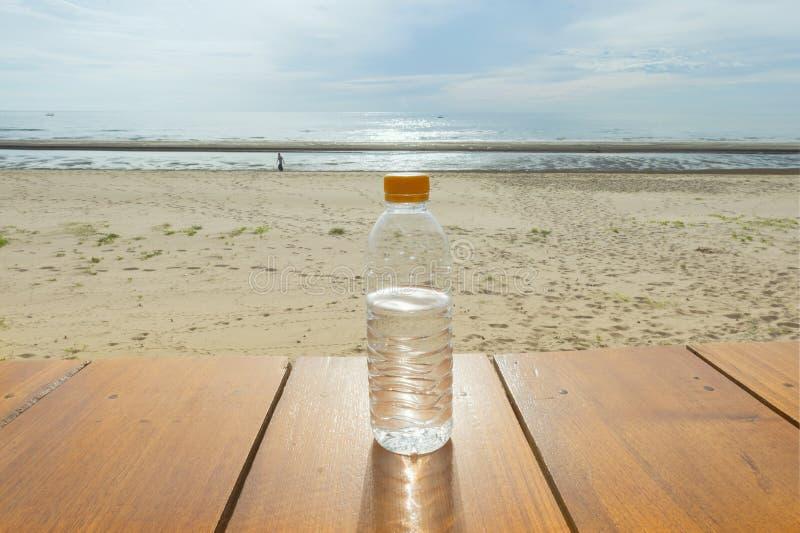 Μπουκάλι νερό στο ξύλινο πάτωμα στην παραλία θάλασσας και το υπόβαθρο μπλε ουρανού στοκ εικόνα