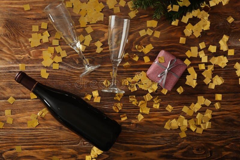 Μπουκάλι της σαμπάνιας με τα γυαλιά και του κιβωτίου δώρων στο ξύλινο υπόβαθρο στοκ φωτογραφία με δικαίωμα ελεύθερης χρήσης