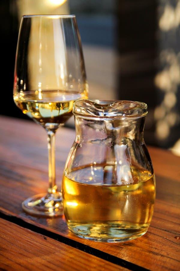 Μπουκάλι του άσπρων κρασιού και του γυαλιού στην ξύλινη επιτραπέζια κορυφή Ποτήρι του κατεψυγμένου άσπρου κρασιού στον πίνακα κον στοκ εικόνες με δικαίωμα ελεύθερης χρήσης