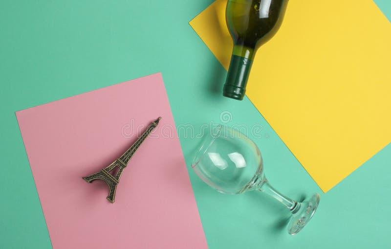 Μπουκάλι του κρασιού, γυαλί, statuette του πύργου του Άιφελ σε ένα χρωματισμένο υπόβαθρο κρητιδογραφιών Τοπ όψη μινιμαλισμός στοκ φωτογραφία με δικαίωμα ελεύθερης χρήσης