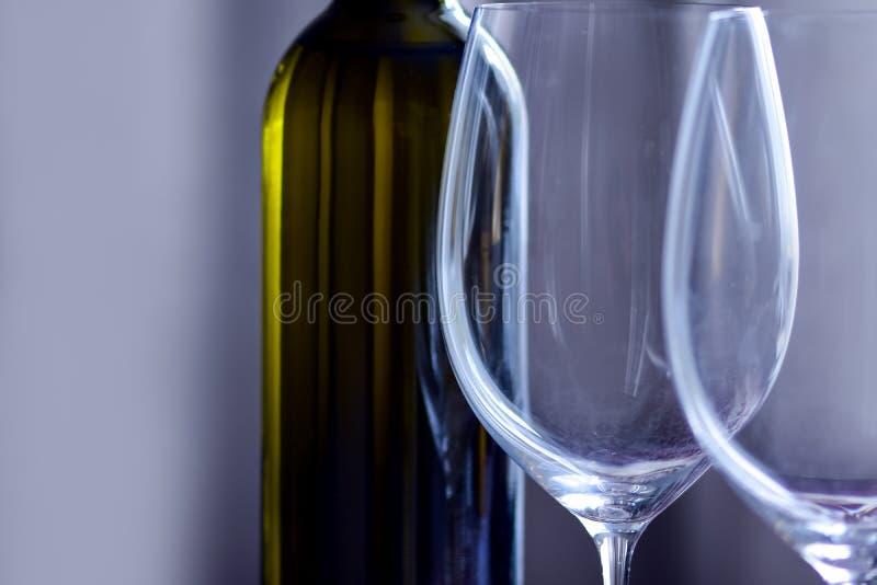 Μπουκάλι του κρασιού και του γυαλιού κρασιού stemware στο απλό εσωτερικό στοκ φωτογραφίες