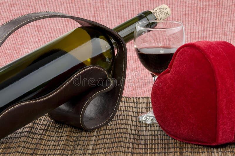 Μπουκάλι του κρασιού, του γυαλιού και του κόκκινου κιβωτίου δώρων καρδιών στοκ εικόνες