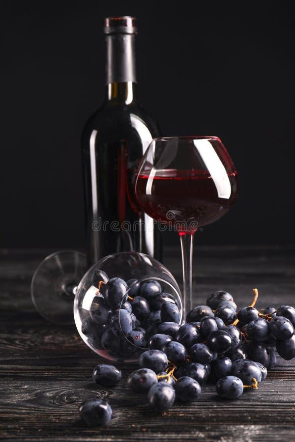 Μπουκάλι του κρασιού, των γυαλιών και των σταφυλιών στο σκοτεινό υπόβαθρο στοκ φωτογραφία με δικαίωμα ελεύθερης χρήσης