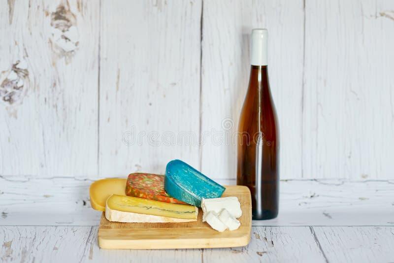 Μπουκάλι του κόκκινου κρασιού και παραλλαγή του τυριού στον ξύλινο πίνακα στοκ φωτογραφίες με δικαίωμα ελεύθερης χρήσης