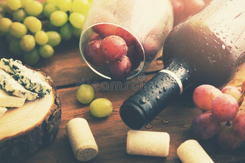 Μπουκάλι του κόκκινου κρασιού με τα σταφύλια και το μπλε τυρί στοκ εικόνες