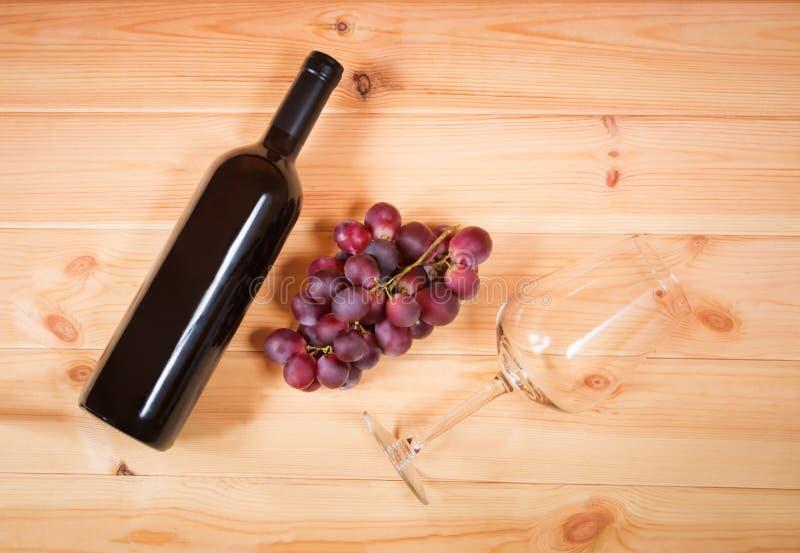 Μπουκάλι του κόκκινου κρασιού, του πορφυρών σταφυλιού και του γυαλιού κρασιού στοκ εικόνες