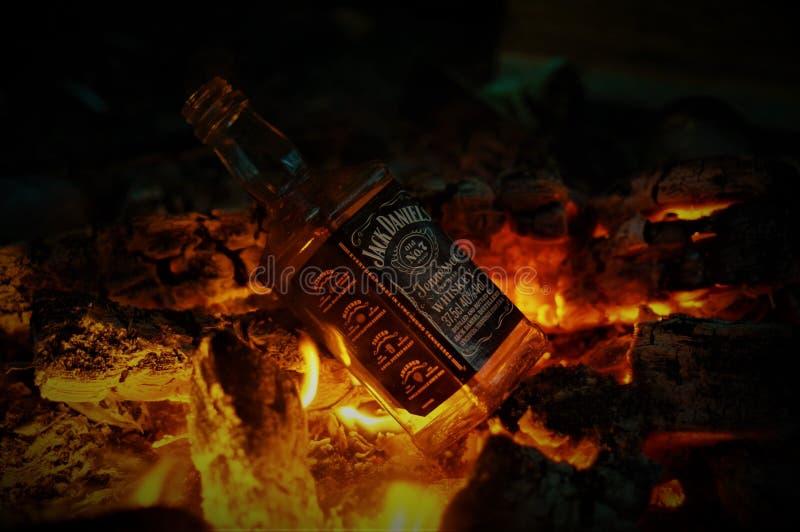 Μπουκάλι του ουίσκυ Jack Ντάνιελ στην πυρκαγιά με το κάψιμο των ξυλανθράκων στη νύχτα στοκ εικόνες