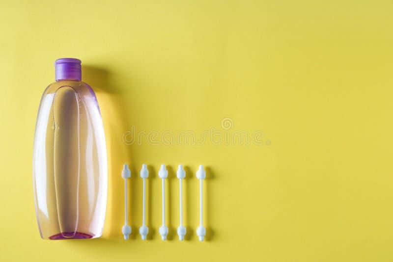 Μπουκάλι του σαμπουάν μωρών με τις πατσαβούρες βαμβακιού στο υπόβαθρο χρώματος στοκ εικόνες