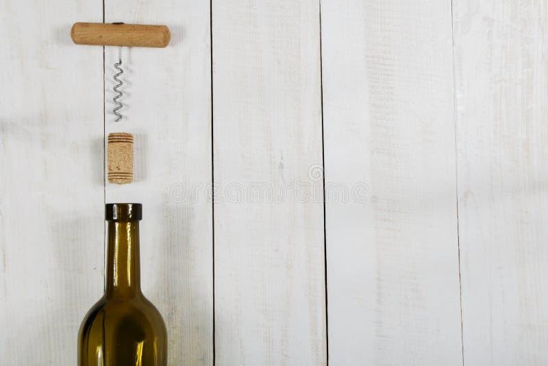 Μπουκάλι του φελλού κρασιού και ένα ανοιχτήρι σε έναν άσπρο ξύλινο πίνακα στοκ φωτογραφίες