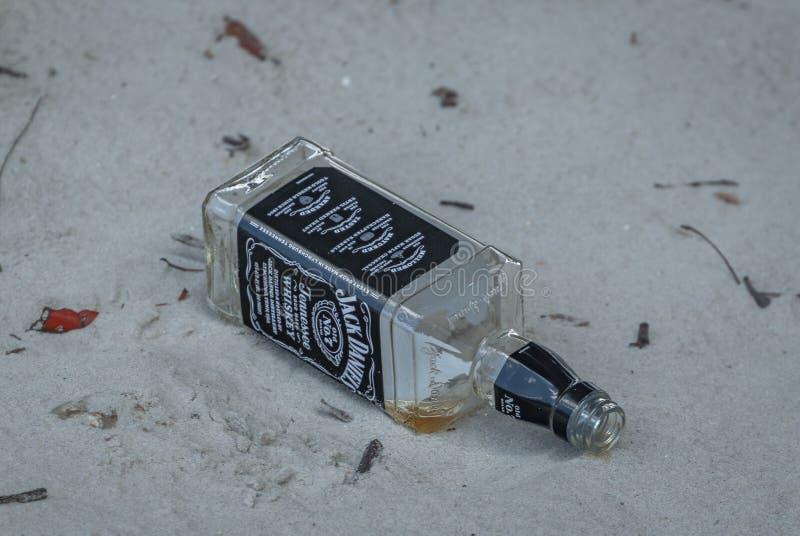 Μπουκάλι του Jack Daniels κενό στην άμμο στοκ εικόνα