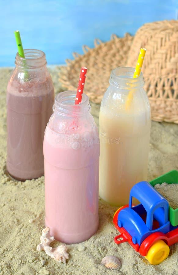 Μπουκάλι τρία της διάφορης σοκολάτας, της φράουλας και της βανίλιας milkshakes Υγιής καταφερτζής με το άχυρο Νόστιμα κοκτέιλ κουν στοκ εικόνα