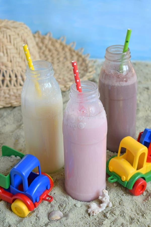 Μπουκάλι τρία της διάφορης σοκολάτας, της φράουλας και της βανίλιας milkshakes Υγιής καταφερτζής με το άχυρο Νόστιμα κοκτέιλ κουν στοκ φωτογραφία με δικαίωμα ελεύθερης χρήσης