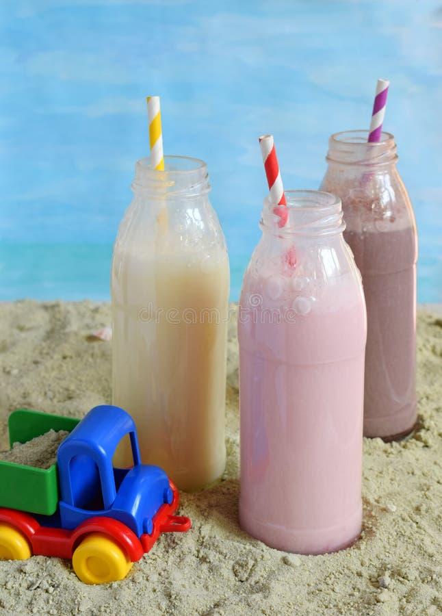 Μπουκάλι τρία της διάφορης σοκολάτας, της φράουλας και της βανίλιας milkshakes Υγιής καταφερτζής με το άχυρο Νόστιμα κοκτέιλ κουν στοκ εικόνα με δικαίωμα ελεύθερης χρήσης