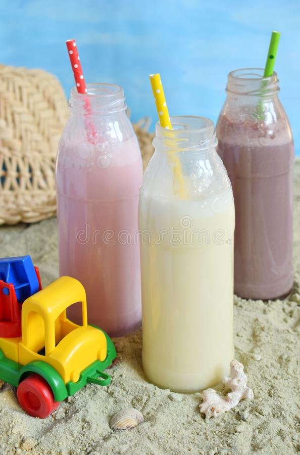 Μπουκάλι τρία της διάφορης σοκολάτας, της φράουλας και της βανίλιας milkshakes Υγιής καταφερτζής με το άχυρο Νόστιμα κοκτέιλ κουν στοκ εικόνες με δικαίωμα ελεύθερης χρήσης
