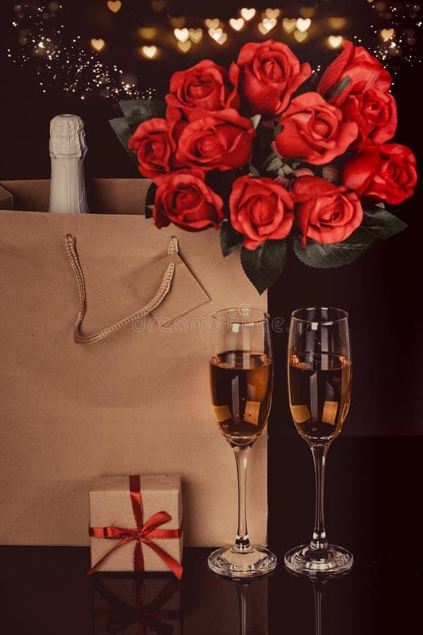 Μπουκάλι CHAMPAGNE, κόκκινα τριαντάφυλλα σε μια τσάντα εγγράφου και δύο γυαλιά κρασιού στοκ εικόνες με δικαίωμα ελεύθερης χρήσης