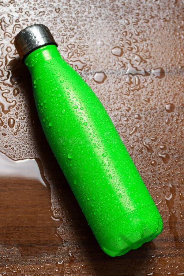 Μπουκάλι thermos ανοξείδωτου που απομονώνεται σε έναν ξύλινο πίνακα που ψεκάζεται με το νερό Ανοικτό πράσινο χρώμα στοκ εικόνες με δικαίωμα ελεύθερης χρήσης