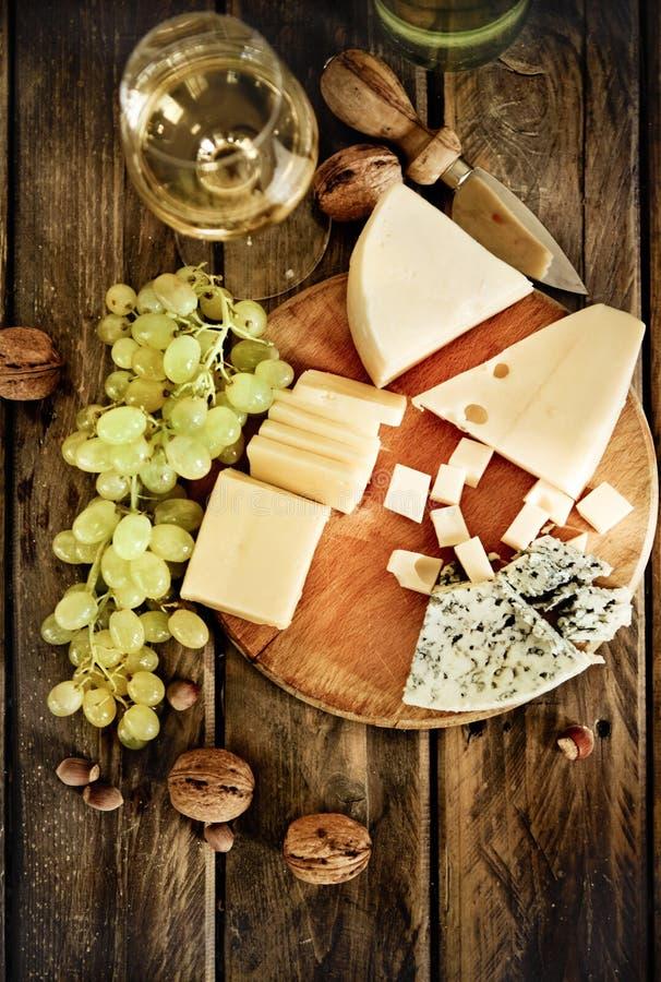 Μπουκάλια και ποτήρι του άσπρων κρασιού, του τυριού, των καρυδιών και των σταφυλιών στοκ εικόνα